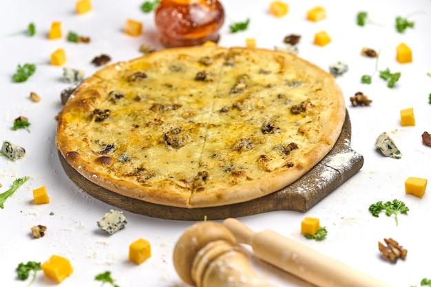 Gesneden zelfgemaakte pizza met noten, gorgonzola kaas en walnoten op houten plaat