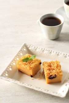 Gesneden zelfgemaakte prol tape of bolu tapai op witte plaat. prol tape is traditionele cake uit indonesië, gemaakt van gefermenteerde cassave, belegd met geraspte kaas en gebakken