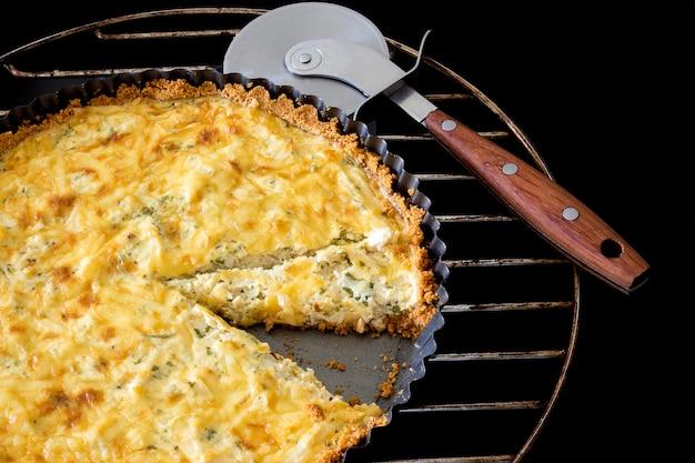 Gesneden zelfgemaakte quiche met kip, kaas en groene ui en peterselie en pizza mes op zwart