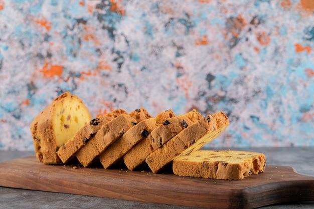 Gesneden zelfgemaakte roulette cake op houten snijplank over grijze tafel.
