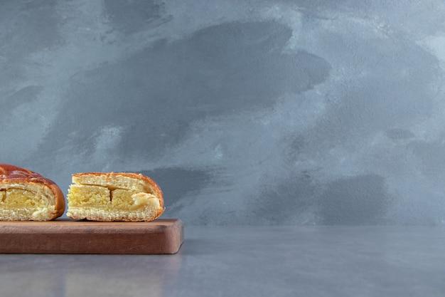 Gesneden zelfgemaakte verse gebakjes op een houten bord.