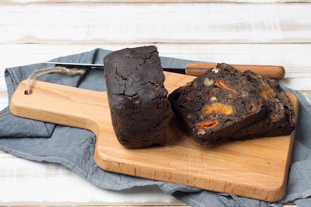 Gesneden zoet dessertbrood met pruimen, abrikozen en walnoten ligt op het keukenbord.