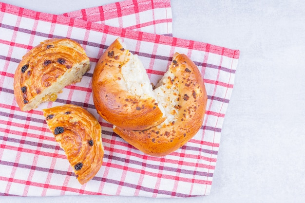 Gesneden zoete broodjes op een theedoek, op het marmer.