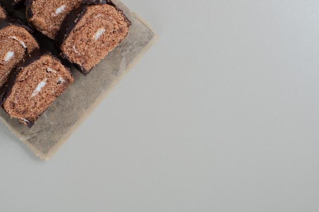 Gesneden zoete chocoladerol op een houten bord.