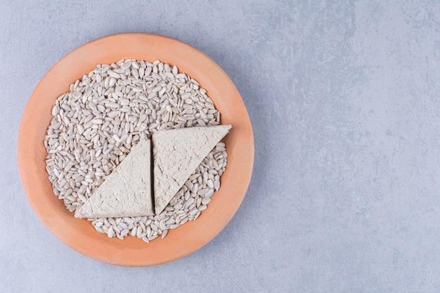 Gesneden zonnebloemhalva en gepeld zaad op een plaat op het marmeren oppervlak