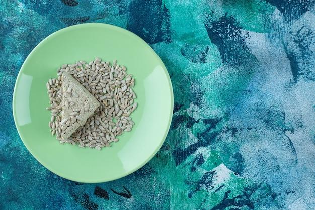 Gesneden zonnebloemhalva met zaden op de plaat, op de marmeren tafel.
