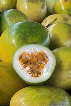 Gesneden zure passievrucht, over stapel hele vruchten