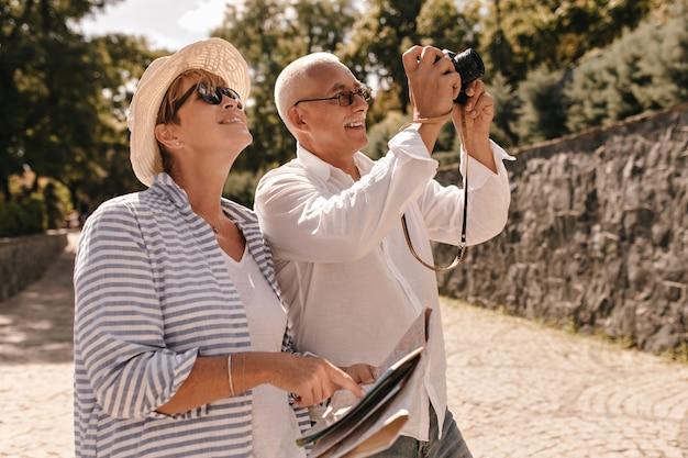 Gesnorde man in glazen en licht overhemd fotograferen en lachend met blonde vrouw in hoed en gestreepte blouse buiten.