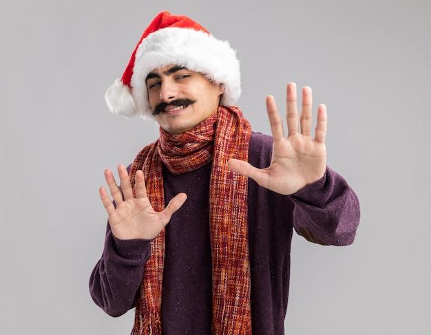 Gesnorde man met kerst kerstmuts met warme sjaal om zijn nek op zoek verward verdediging gebaar met handen maken