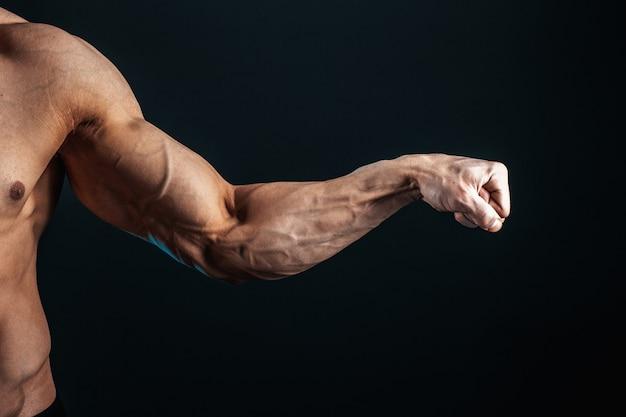 Gespannen arm gebald in vuist, aderen, bodybuilder-spieren op een donkere ruimte, isoleer