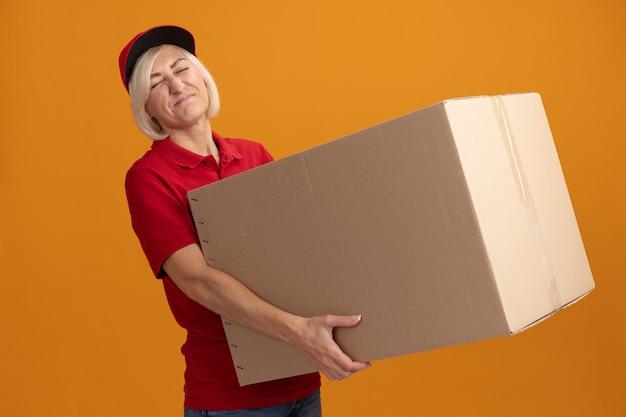 Gespannen blonde bezorger van middelbare leeftijd in rood uniform en pet met kartonnen doos met gesloten ogen geïsoleerd op oranje muur
