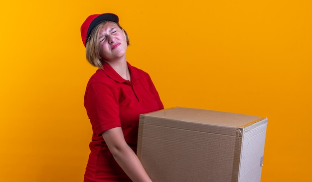 Gespannen, jonge bezorger, gekleed in uniform met dop met doos geïsoleerd op een oranje muur