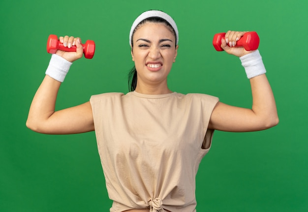 Gespannen jonge kaukasische sportieve vrouw die hoofdband en polsbanden draagt en naar voren kijkt die dumbbells opheft die op groene muur worden geïsoleerd