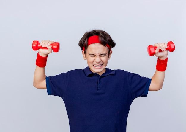 Gespannen jonge knappe sportieve jongen dragen hoofdband en polsbandjes met beugels verhogen halters met gesloten ogen geïsoleerd op witte achtergrond