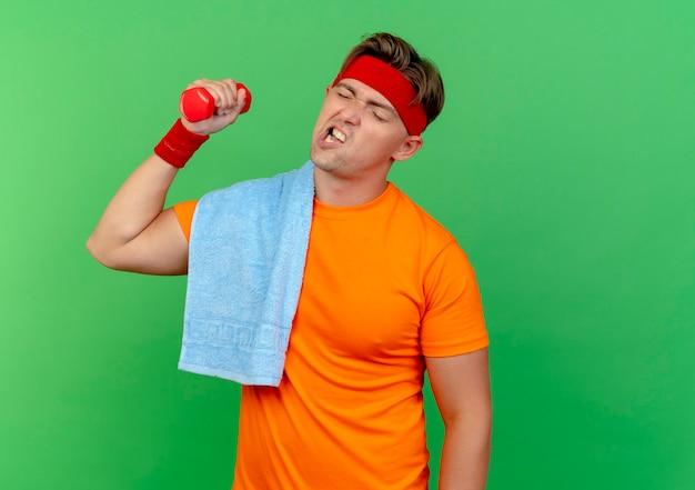 Gespannen jonge knappe sportieve man met hoofdband en polsbandjes met handdoek op schouder opheffen halter geïsoleerd op groene muur