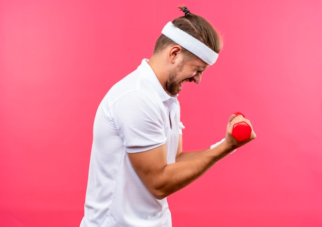 Gespannen jonge knappe sportieve man met hoofdband en polsbandjes staande in profiel te bekijken met halters met gesloten ogen geïsoleerd op roze ruimte