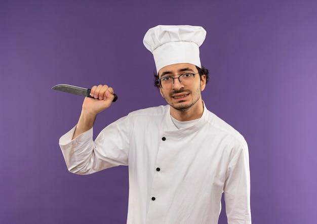 Gespannen jonge mannelijke kok die eenvormige chef-kok en glazen draagt die mes op purple houden