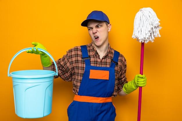 Gespannen jonge schoonmaakster met uniform en pet met handschoenen die een dweil vasthoudt en naar een emmer in zijn hand kijkt