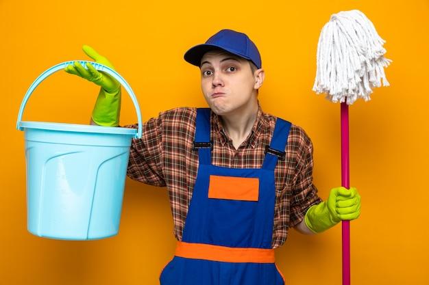 Gespannen jonge schoonmaakster met uniform en pet met handschoenen met dweil en emmer