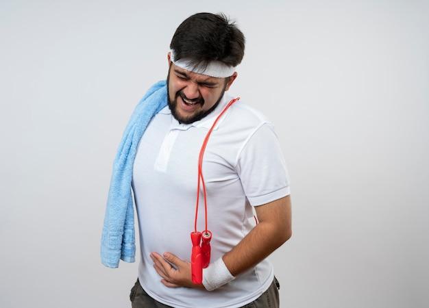 Gespannen jonge sportieve man met hoofdband en polsband met handdoek en springtouw op schouder hand op maag zetten geïsoleerd op een witte muur