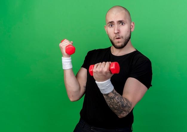 Gespannen jonge sportieve man met polsbandje oefenen met halters geïsoleerd op groen