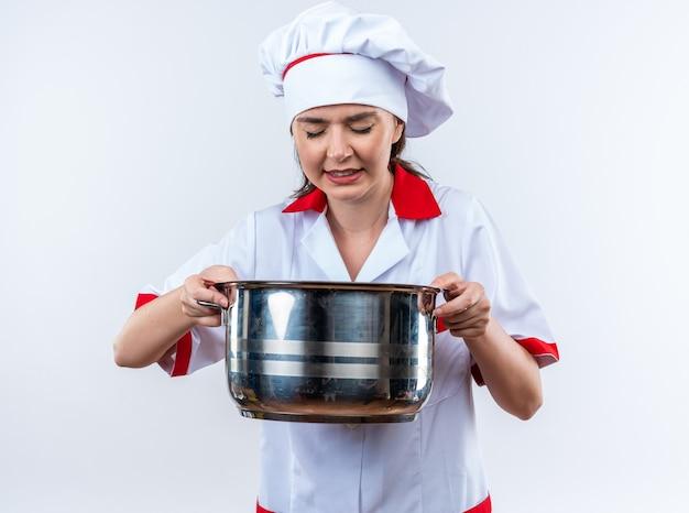 Gespannen jonge vrouwelijke kok die chef-kok uniform draagt die steelpan houdt die op witte achtergrond wordt geïsoleerd