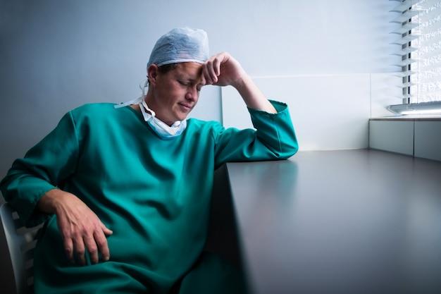 Gespannen mannelijke chirurgzitting bij venster