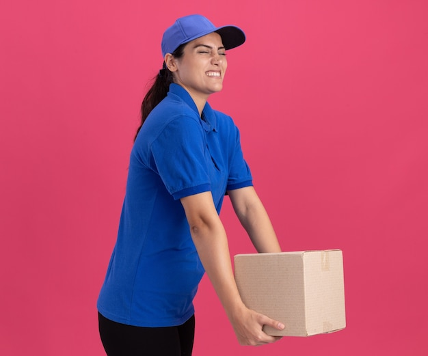 Gespannen met gesloten ogen jong leveringsmeisje die eenvormig met glb-holdingsdoos dragen die op roze muur wordt geïsoleerd