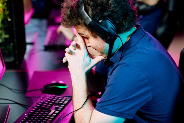 Gespannen of bezorgde jonge man in hoofdtelefoon wat betreft gezicht terwijl lichtjes bukken toetsenbord voor computermonitor