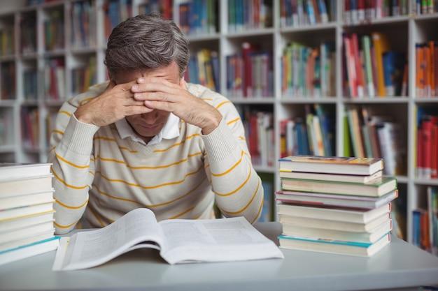 Gespannen schoolleraar die in bibliotheek studeert
