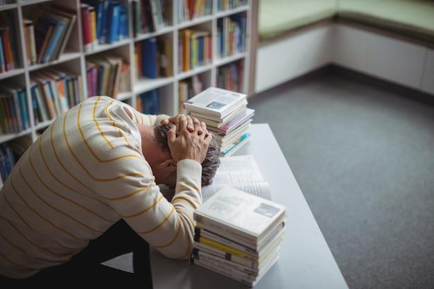 Gespannen schoolleraar leunend op tafel in bibliotheek