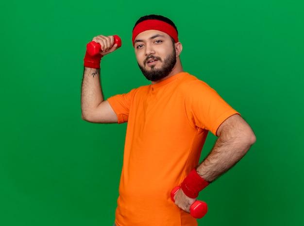 Gespannen sportieve jongeman met hoofdband en polsband hand op heup zetten en halters geïsoleerd op groene achtergrond te houden
