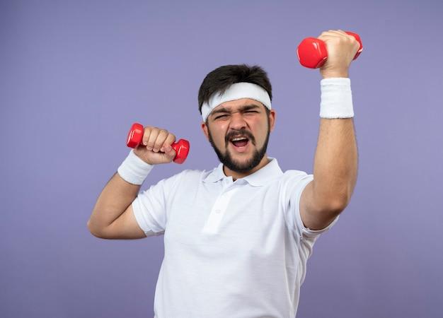 Gespannen sportieve jongeman met hoofdband en polsband trainen met halters geïsoleerd op groene muur