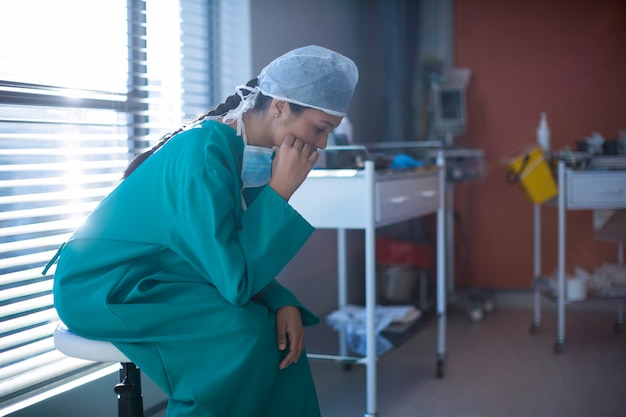 Gespannen vrouwelijke chirurg die in afdeling zit