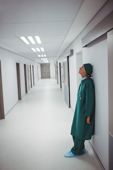 Gespannen vrouwelijke chirurg die op muur in gang leunt