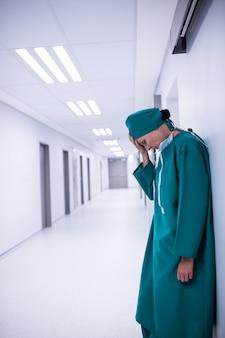 Gespannen vrouwelijke chirurg die zich in gang bevindt