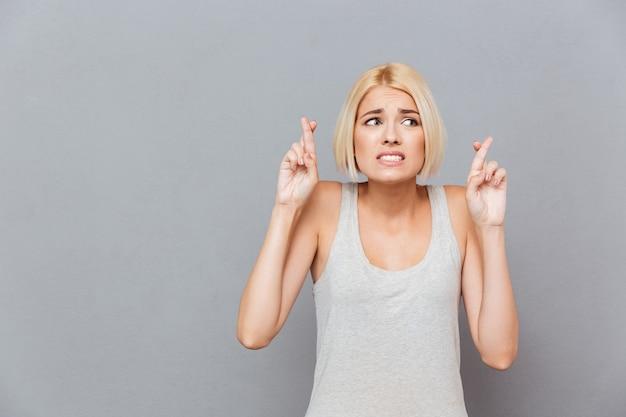Gespannen zenuwachtige jonge vrouw die zich met gekruiste vingers bevindt