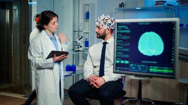 Gespecialiseerde arts in de neurowetenschappen die aantekeningen maakt op het klembord tijdens het testen van de hersenfuncties van de mens met behulp van een eeg-headset, het behandelen van disfuncties van het zenuwstelsel in een modern laboratorium
