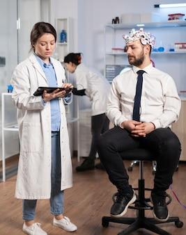 Gespecialiseerde arts in de neurowetenschappen die aantekeningen maakt op het klembord tijdens het testen van hersenfuncties van de mens met behulp van een eeg-headset, waarbij stoornissen van het zenuwstelsel worden behandeld in een modern laboratorium.