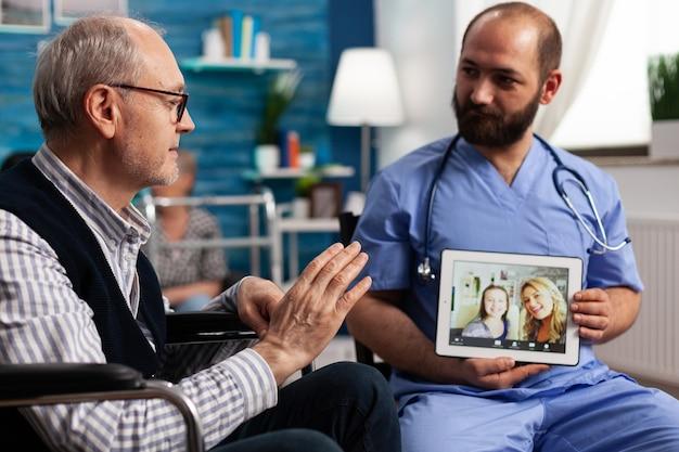 Gespecialiseerde assistent-man met tabletcomputer in handen terwijl gepensioneerde mannelijke patiënt vrienden begroet
