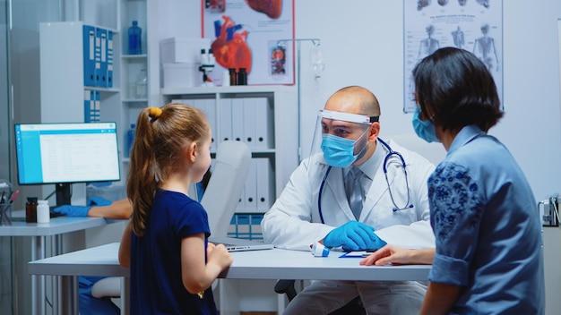 Gespecialiseerde dokter die de temperatuur van het kind meet tijdens een pandemie van het coronavirus. gezondheid kinderarts specialist het verstrekken van gezondheidszorg consultaties behandeling in beschermende uitrusting voor consultatie