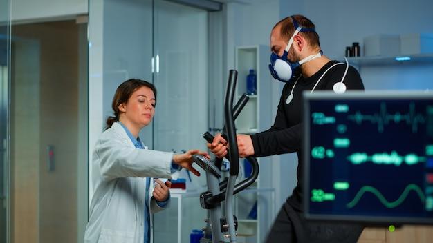 Gespecialiseerde gezondheidssupervisor verhoogt het niveau van oefeningen die het uithoudingsvermogen van de atleet bewaken. medisch onderzoeker die vo2 meet van prestatiesporten die met masker op crosstrainer in sportlab lopen
