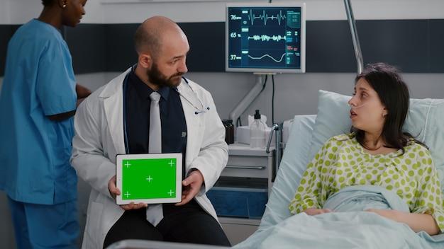Gespecialiseerde man in witte jas praat met zieke vrouw over behandeling voor ziekteherstel