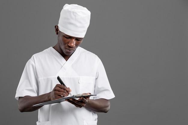 Gespecialiseerde mannelijke arts die zijn nota's schrijft