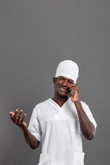 Gespecialiseerde mannelijke arts glimlacht en praat over de telefoon
