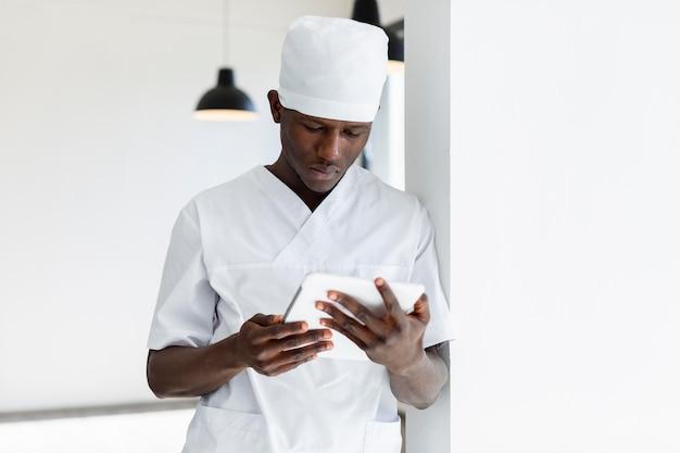 Gespecialiseerde mannelijke arts met behulp van een digitale tablet