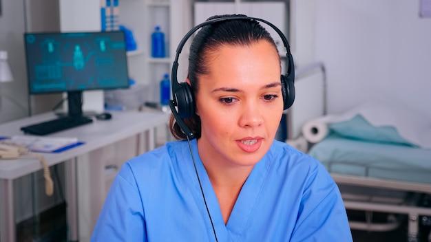 Gespecialiseerde verpleegkundige beantwoordt met behulp van een koptelefoon die de afspraak controleert tijdens telehealth-communicatie in het ziekenhuis. arts in de medische kliniek, receptioniste arts-assistent helpt met concul