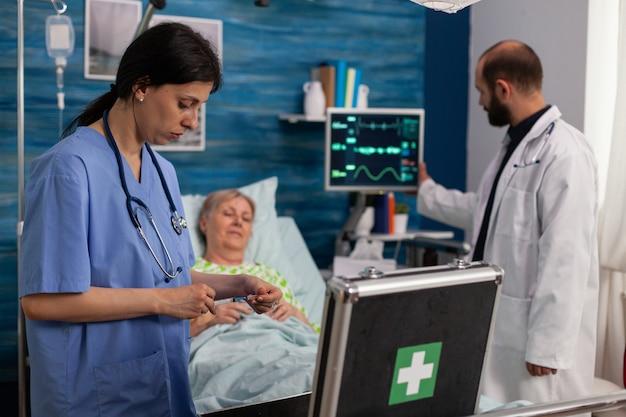Gespecialiseerde vrouwelijke verpleegster die naar de zak met medicijnkit kijkt terwijl de man-verpleegster voor sociale ondersteuning