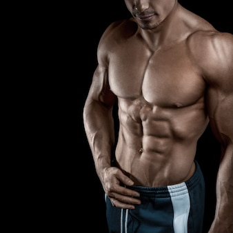 Gespierd en fit jonge bodybuilder fitness mannelijk model poseren over zwart