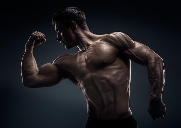 Gespierd en fit jonge bodybuilder fitness mannelijk model poseren.